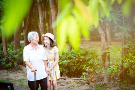 Asian little girl supporting senior woman with walking stick,happy smiling grandmother and granddaughter in the park,elderly people walking exercise for health,concept family;summer and vacation Stockfoto