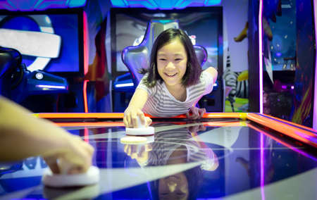Asian little girl playing arcade game on the computer machines at the shopping mall outlets,holiday activities of cute child play games,slot machines in the mall center,vacation concept