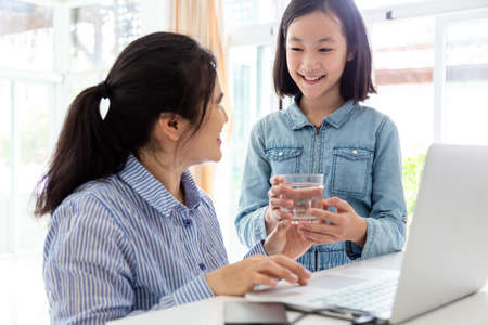 Cute daughter giving or serving cups of water for mother to drink,Asian business woman working with fatigue,surfing the internet with laptop computer at table in home,technology and family concept