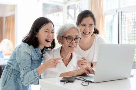 Matka i córka surfują po Internecie; oglądają coś interesującego z babcią, szczęśliwą uśmiechniętą azjatycką starszą kobietą, podczas gdy jej córka i wnuczka używają laptopa przy stole w domu, koncepcja rodziny, technologia Zdjęcie Seryjne