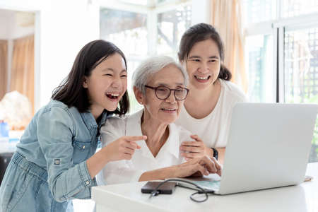 Mother and daughter surfing the internet;watching something interesting with grandmother,happy smiling asian senior woman while her daughter and granddaughter using laptop computer at table in home,concept family,technology