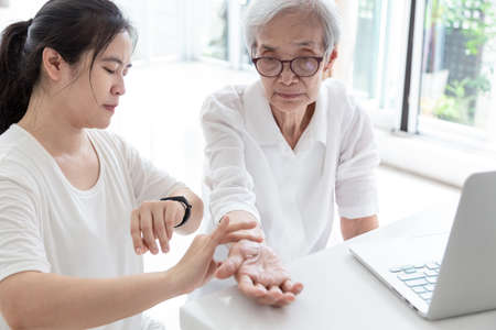 Female doctor or nurse is checking senior woman patience's pulse by fingers,caregivers or nursing assistants measuring patient pulse,elderly woman,medical check health in home
