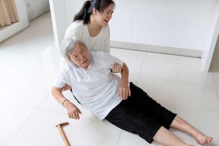 Asiatische ältere Menschen mit Gehstock auf dem Boden, nachdem sie hingefallen waren und sich um eine junge Assistentin gekümmert hatten, eine kranke ältere Frau fiel wegen Schwindel, Ohnmacht, Krankheit und einer Tochter, die ihr hilft und sich um sie kümmerte, zu Boden