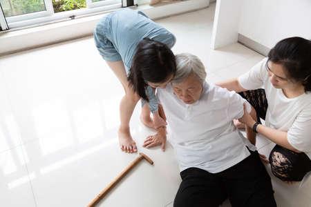 바닥에 지팡이를 짚고 넘어지고 돌보는 젊은 여성 조수, 아픈 노인 여성 또는 어머니는 현기증, 기절, 질병으로 고통받고 딸, 손녀가 도와주고 돌봐주기 때문에 바닥에 쓰러진 아시아 노인