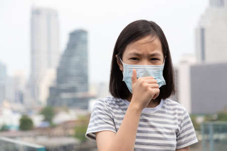 Asian little girl suffer from cough with face mask protection,cute child wearing face mask because of air pollution in the city building as background,Sick girl with medical mask;concept of pollution,dust allergies and health Stock Photo