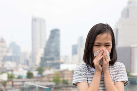 portrait of cute little girl blowing nose in paper handkerchief,Asian child sneezing in a tissue in the city building as background, concept of pollution,dust allergies and health Stock Photo