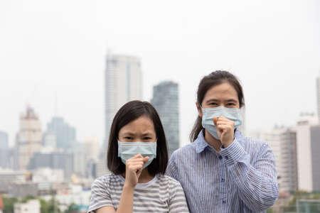 Donne asiatiche o madre e figlia soffrono di tosse con protezione della maschera facciale, bambino carino e donna adulta che indossa una maschera facciale a causa dell'inquinamento atmosferico nell'edificio della città come sfondo, ragazza malata con maschera medica; concetto di inquinamento, allergie alla polvere e salute