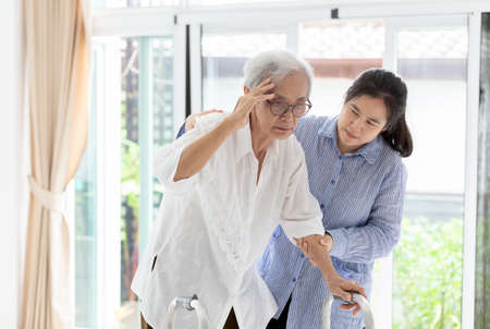 Asian daughter or care assistant helping support senior woman or mother,communicates the symptoms of vertigo;dizziness;migraine;sick depressed,suffering from headache,old woman in using walker during rehabilitation,concept elderly care