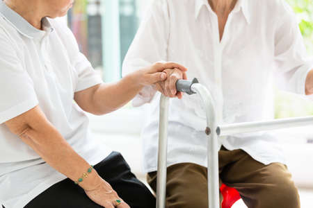 Two asian senior women friends holding hands for care,help and support her friend,time together,old people with walker during rehabilitation at home,friendship of the elderly,retirement age Stock Photo