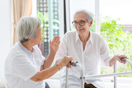 Happy two asian senior women friends holding hands for care,support and fun talking,time together,old people smiling with walker during rehabilitation at home,friendship of the elderly,retirement age