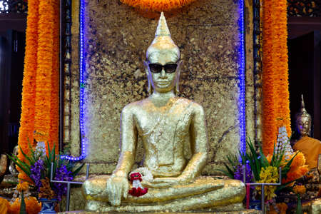 Unseen Thailand,the ancient golden buddha statue wearing black glasses with dark lenses or sunglasses,is a place and sacred buddha image that is popular with local people at Wat Krok Krak,travel in Samut Sakhon near Bangkok,Thailand