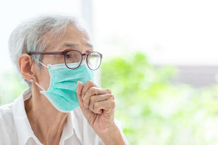 Asian senior woman suffer from cough with face mask protection,elderly woman wearing face mask because of air pollution,Sick old people with medical mask;concept of pollution,dust allergies and health
