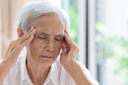 Asian senior woman has headache,touching her head with her hands,communicates the symptoms of vertigo;dizziness;migraine;sick depressed,elderly people suffering from headache pain or memory loss and feeling unwell Archivio Fotografico