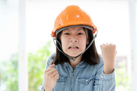 Angry asian little girl hand with fist gesture with safety helmet or hard hat,closeup portrait of cute child shows fist,having emotions,feelings,aggression concept Stock Photo