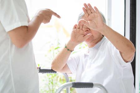 La donna anziana asiatica è stata abusata fisicamente, attaccando in casa, l'uomo arrabbiato ha alzato il pugno di punizione, ferma l'abuso fisico persone anziane, badante, famiglia ferma la violenza e il concetto di aggressione