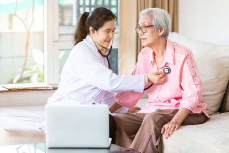 Family doctor or nurse checking smiling senior patient using stethoscope during home visit,young female home caregiver,health visitor examining asian elderly woman,healthcare medicine concept Stock Photo