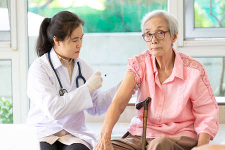 Asian female doctor with syringe doing injection vaccine,flu,influenza in the shoulder or arm of senior woman,young nurse injecting,vaccinating elderly patient,vaccination,medicine,health care concept Standard-Bild
