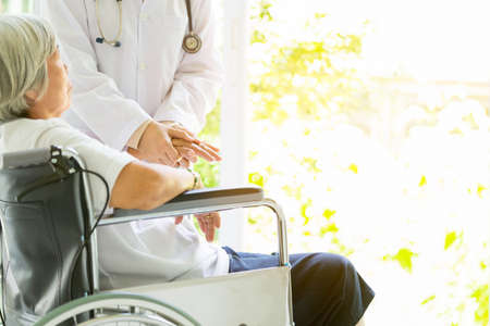 Caring doctor or nurse supporting disabled senior asian woman on wheelchair in hospital,female caregiver holding elderly patient's hand comforting during illness,help,health care concept 版權商用圖片