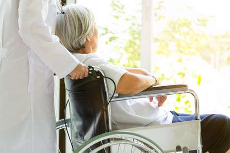 Cuidado médico o enfermera que apoya discapacitados, mujer asiática mayor de alzheimer en silla de ruedas, cuidadora caminando, paciente anciano con síntomas depresivos que necesitan atención cercana, atención médica, concepto de depresión