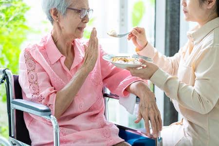 """Donna anziana asiatica infelice che rifiuta, gesto della mano """"NO"""" paziente anziano annoiato dal cibo o dalla noia, anziani che si ammalano e si stancano del cibo in sedia a rotelle a casa, perdita di appetito, concetto di anoressia"""