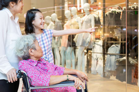 Asian senior woman or mother with her daughter and smiling of child girl or granddaughter looking at shop in shopping mall together,elderly woman in wheelchair with their family,happy family,vacation concept 版權商用圖片