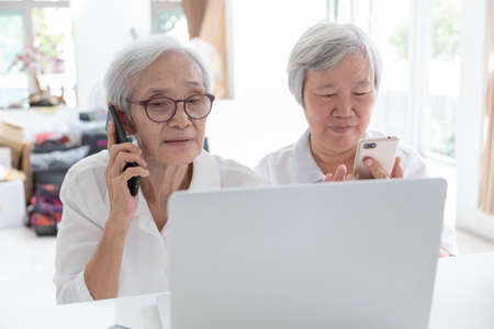Asian senior woman and friend with laptop computer,happy smiling elderly people watching something interesting while holding the phone,talking about financial business in home,technology concept 写真素材