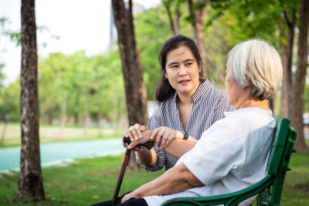 Elderly woman or mother with depressive symptoms or alzheimer patient,asian female caregiver or daughter holding elderly patient's hand comforting,support in outdoor park feeling sad,depression concept