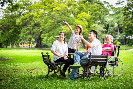 Joyeuse famille asiatique, père, mère, fille regardant quelque chose d'intéressant avec une grand-mère âgée en fauteuil roulant dans un parc extérieur, une femme âgée souriante et souriante se détend, s'amuse à parler dans le jardin, concept de famille, été et vacances Banque d'images