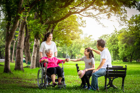 Happy asian family,support,care,talk,little child girl or granddaughter holding hands with senior grandmother,father,mother having fun,laugh,smile,elderly in wheelchair with her family in outdoor park,multi generation concept