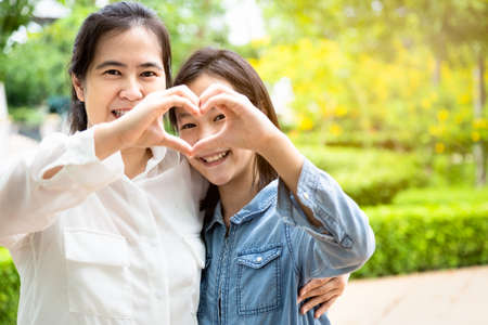 Happy beautiful asian adult woman and cute child girl forming a heart with their hands while hugging and smiling in garden,love of mother with her little daughter in outdoor park in nature,mother's day, family, love concept