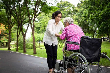 Female caregiver asian or adult nurse support,helping senior woman to stand up from wheelchair in outdoor park,patient mother with her daughter in summer green nature, family ,elderly care concept