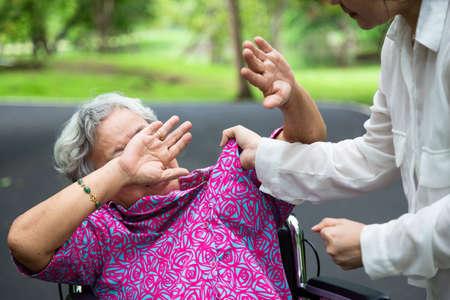 Asiatische ältere Frauen wurden im Rollstuhl körperlich missbraucht, griffen im Park an, wütende junge Frau hob die Straffaust, stoppte körperliche Misshandlung älterer Menschen, Betreuer, Familie stoppte Gewalt und Aggressionskonzept