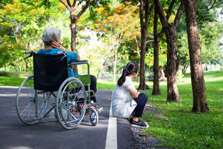 Asian adult woman touchy and angry acting with elderly people in wheelchair after senior mother argument,argue with daughter in outdoor park,relationship difficulties,conflict,hurt,family problems concept