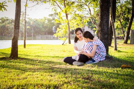 Une mère asiatique donne des conseils, parle à sa fille pour l'encourager, une enfant triste qui pleure, la décourage et la maman réconforte dans un parc extérieur d'été, les soins, l'amour, la vie de famille et le concept de consultation Banque d'images