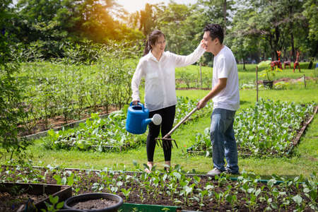 Happy asian couple gardeners,wife help,care,wipe sweat for husband in farm,man working using rake in organic garden,woman with watering can in vegetables garden,gardening,agriculture,activites grow vegetables