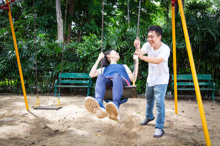 Happy asian little child girl having fun,enjoy,playful,playing on the swing,beautiful daughter riding on swing in playground,smiling father pushing,dad swinging her in outdoor park,vacation family concept Stock Photo