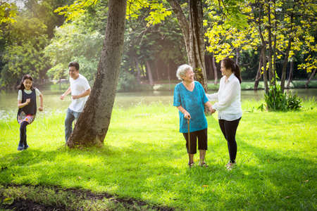 Happy family,asian little child girl or daughter playing touch,tag game,fun,running with father,senior grandmother and mother having smile,laugh in outdoor park,parents enjoy,summer vacation concept