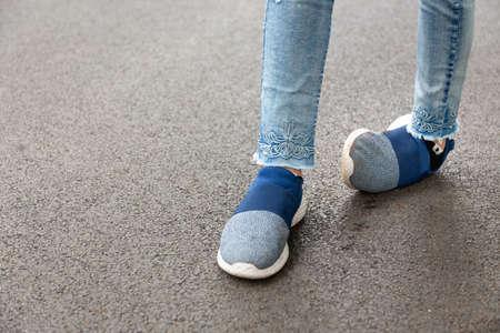 Infirme, femme handicapée, personnes handicapées ou entorse accidentelle à la cheville en faisant du jogging, course dans un parc extérieur, douleur ressentie, blessure au pied d'une fillette asiatique causée par l'exercice ou la marche, trébuchement, trébuchement entorse à la cheville