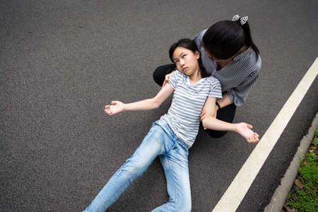 Bambina malata con crisi epilettiche per strada, figlia che soffre di convulsioni, malattia con epilessia durante attacco convulsivo, giovane donna asiatica o cura della madre di una paziente, cervello, concetto di sistema nervoso