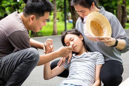 Asiatisches kleines Kind mit Hitzschlag, hohe Temperatur, Schwindel, Schwindel, kranke Tochter an einem sonnigen Tag, süßes Mädchen, das im Sommer im Freien sehr heiß unter Sonnenbrand leidet, sich schwach fühlt, Vater und Mutter helfen, helfen, sich um sie kümmern Standard-Bild