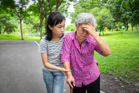 Asiatische ältere Großmutter hat Kopfschmerzen, berührt ihren Kopf mit den Händen, Schwindel, Schwindel, kranke ältere Menschen, hoher Blutdruck, Ohnmacht, Kindermädchen oder Enkelin Pflege, Hilfe, Unterstützung im Freien