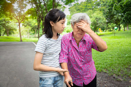 Asian senior grandmother has headache,touching her head with her hands,vertigo;dizziness;sick elderly woman having heat stroke,sunburn,feel faint,child girl or granddaughter care,help,support in outdoor