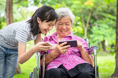 Happy asian senior grandmother and little child girl using cellphone together,playing video game on smart phone,smiling elderly woman in wheelchair,granddaughter having fun,talk in outdoor park,family relationship,technology concept