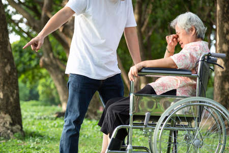 Unhappy,problems asian family,angry man or male caregiver expelled his elderly woman in wheelchair quarrel,arguing,senior mother crying in outdoor,aggressive son,family,violence,ungrateful concept Stock Photo