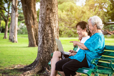Happy asian granddaughter enjoy smiling and senior grandmother with laptop computer,child girl watching something or teaching and showing new computer technology with their elderly woman while relaxing at outdoor park