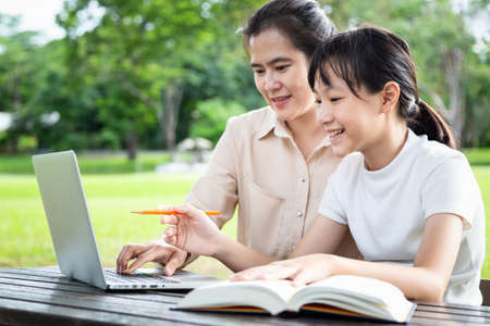 Happy asian family,mother,daughter enjoying using laptop computer in outdoor park, female tutor or teacher working,teaching child girl how to learning,student is interested in studying having fun,tutoring school,education concept