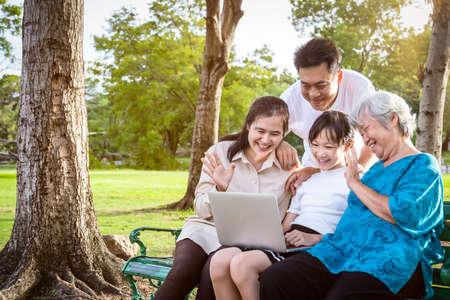 Happy asian family,father,mother,daughter enjoy smiling and senior grandmother using video conferencing with laptop computer,parent,child girl, having video call,talking,saying hi at outdoor park,technology concept Stock Photo