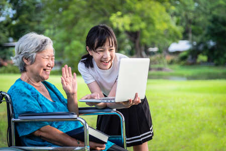 Happy asian granddaughter enjoy smiling and senior grandmother using video conferencing with laptop computer,child girl having video call,waving her hand,saying hi with their elderly woman in wheelchair at outdoor park,technology concept