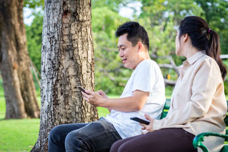 Asian couple,jealous woman with mistrust,noticing,peeking,young man holding mobile phone texting,chatting on smartphone with other girl,wife suspects that her husband is unfaithful,relationship problem and distrust