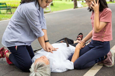 Asian mother first aid emergency CPR on unconscious senior grandmother while daughter calling ambulance,woman try to resuscitation patient,after accident,heart attack,elderly female with cardiac arrest while exercise in park